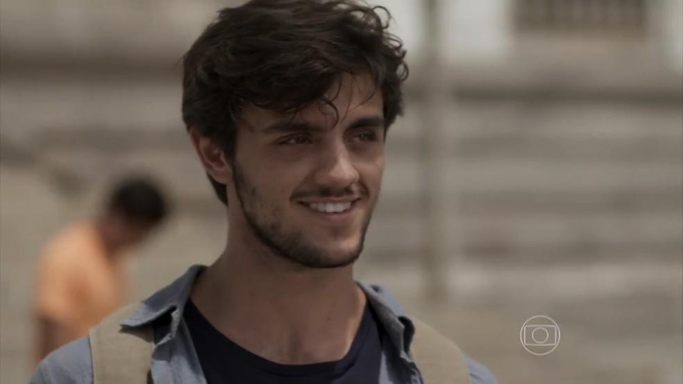 Jonatas (Felipe Simas) fica todo sorridente ao ganhar uma flor da ruivinha — Foto: TV Globo