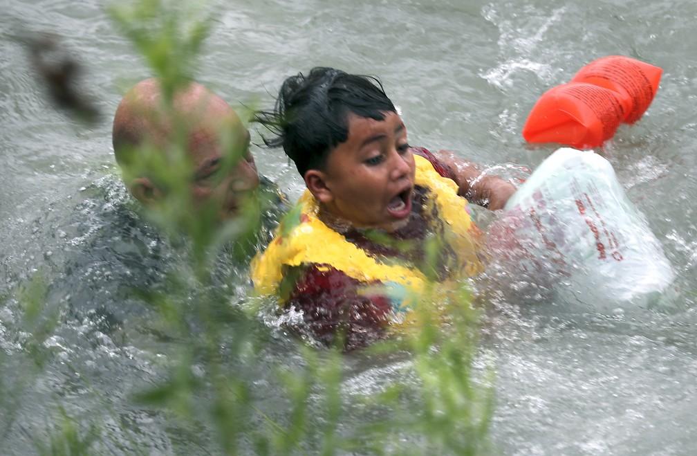 Um menino hondurenho de 7 anos foi resgatado, no dia 10 de maio, por agentes da fronteira no Rio Grande, na fronteira entre Estados Unidos e México. — Foto: Bob Owen/The San Antonio Express-News via AP
