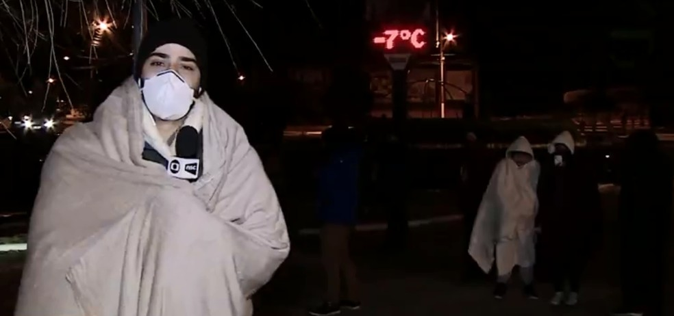Jornalista da NSC TV ganha manta de turista e usa durante telejornal — Foto: NSC TV/Reprodução