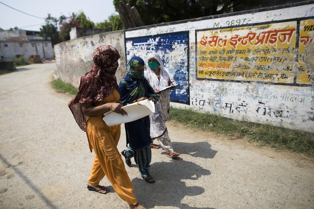 Grupo de mulheres anda de bairro em bairro na Índia para prestar auxílio durante pandemia de Covid-19 — Foto: Xavier Galiana/AFP