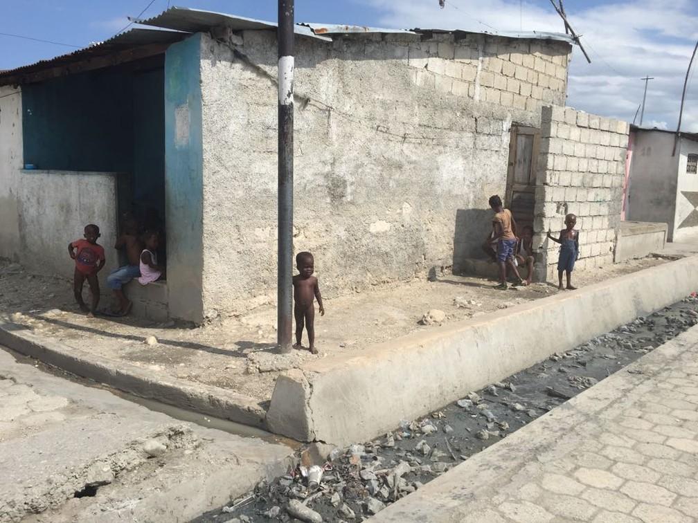 Crianças andam por Cité Soleil, no Haiti, em meio à sujeira (Foto: Tahiane Stochero/ G1)