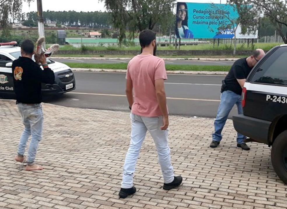 Suspeito (à esq.) tenta esconder o rosto com os tênis enquanto era transferido para a cadeia de São Pedro do Turvo — Foto: Renata Tibúrcio/Arquivo pessoal