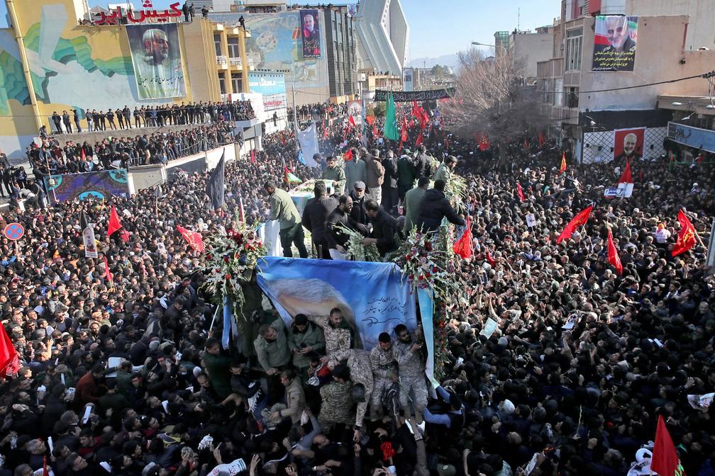 Caixões do general Qassem Soleimani e outras vítimas de ataque no Iraque são transportados por caminhão cercado por multidão em Kerman, no Irã, nesta terça-feira (7)  — Foto: Erfan Kouchari / Agência de Notícias Tasnim via AP
