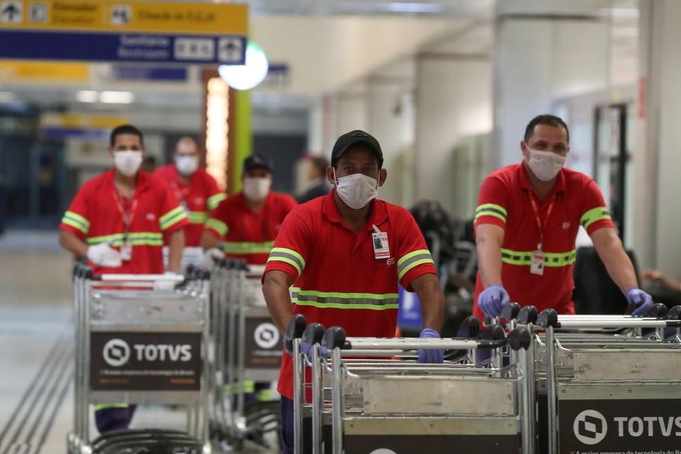 Funcionários do aeroporto de Guarulhos  usam máscaras para se proteger do novo coronavírus — Foto: Amanda Perobelli/Reuters