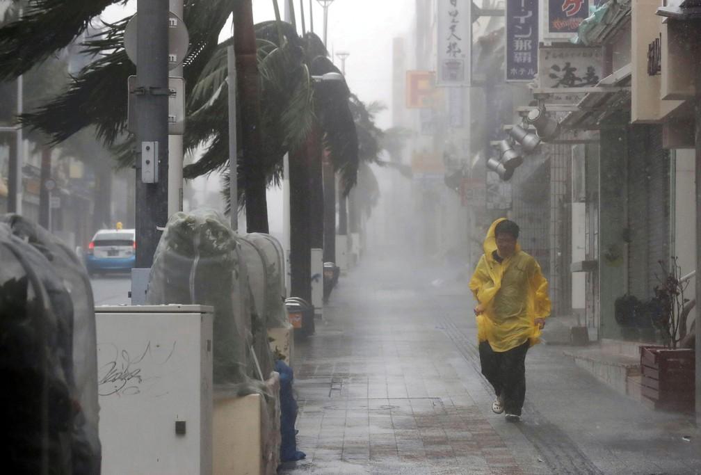 Homem caminha sob forte chuva e ventos provocados pela passagem do tufão Trami por Naha, na ilha de Okinawa, neste sábado (29)  — Foto: Kyodo / via REUTERS