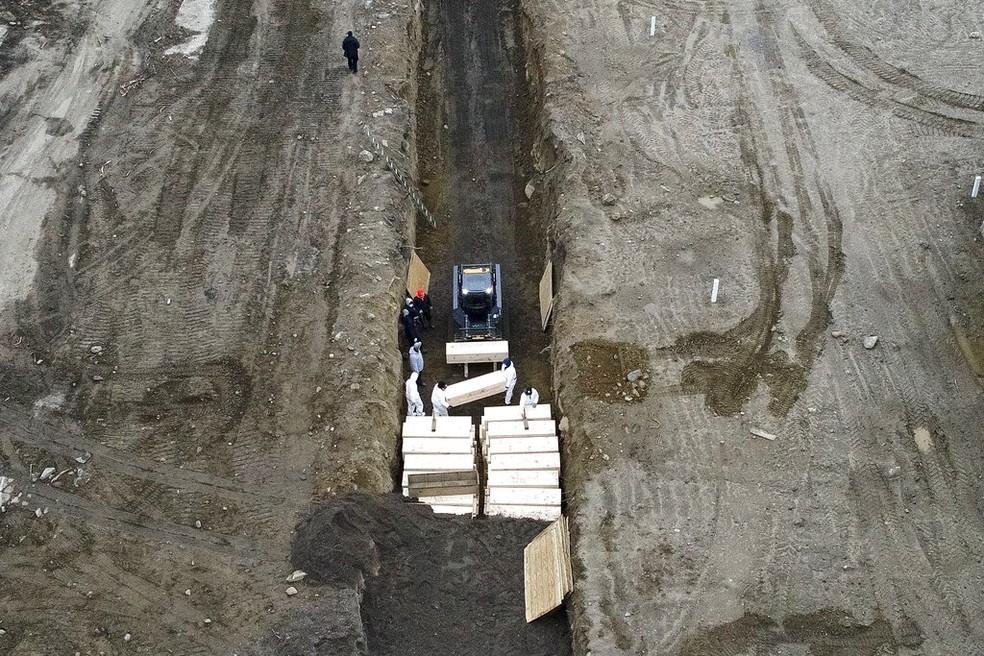 Trabalhadores enterram corpos em uma vala em Hart Island, no bairro do Bronx, em Nova York. — Foto: AP Photo/John Minchillo