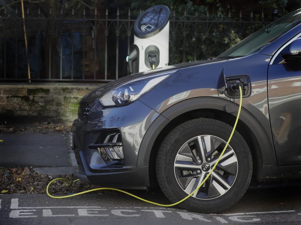 Carro elétrico é carregado em rua de Londres. Governo britânico vai proibir a venda de novos carros a gasolina e diesel a partir de 2030 — Foto: Kirsty Wigglesworth/AP