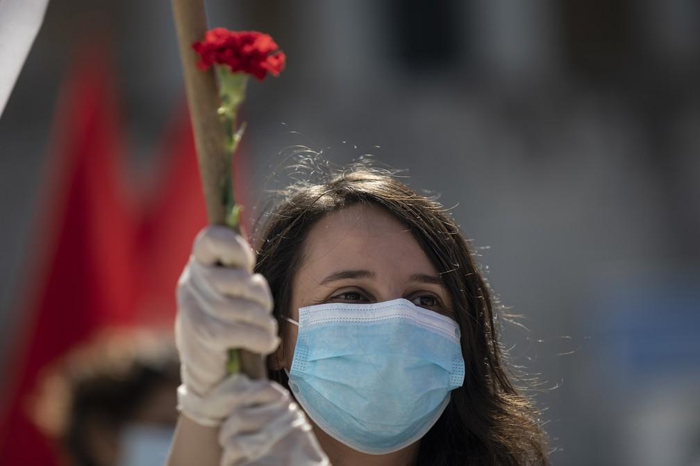 Manifestante com máscara de proteção participa de comício durante o Dia Internacional do Trabalho, em Atenas — Foto: Petros Giannakouris/AP