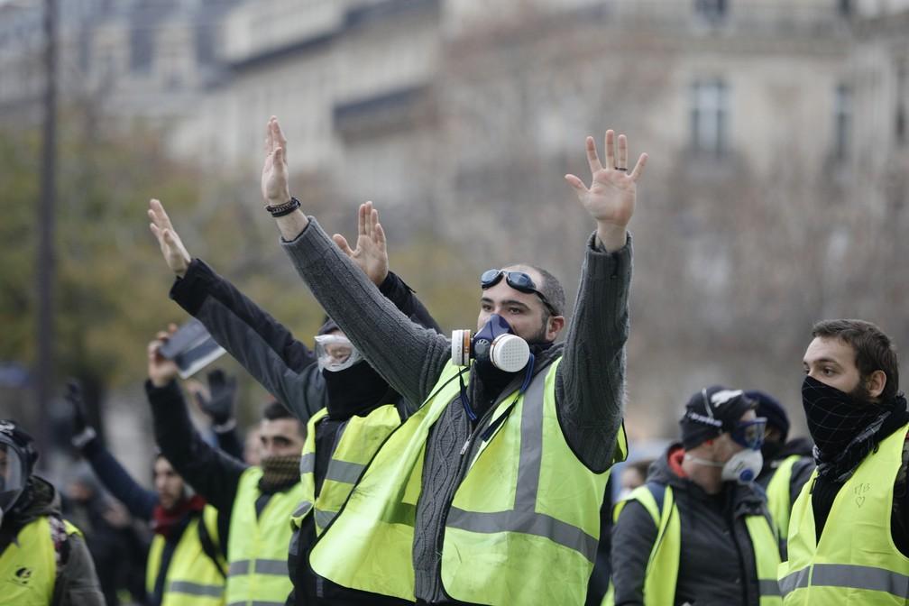 Manifestantes de coletes amarelos protestam contra o aumento de impostos do governo Macron neste sábado (1) na avenida Champs-Elysées, em Paris. — Foto: Kamil Zihnioglu/AP