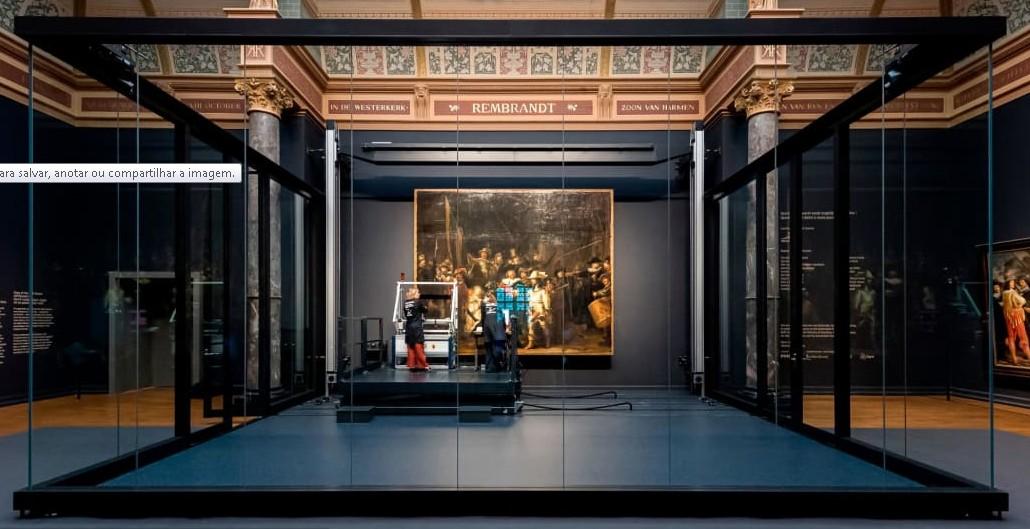 A tela 'Ronda noturna' cercada pela estrutura de vidro durante restauração no museu