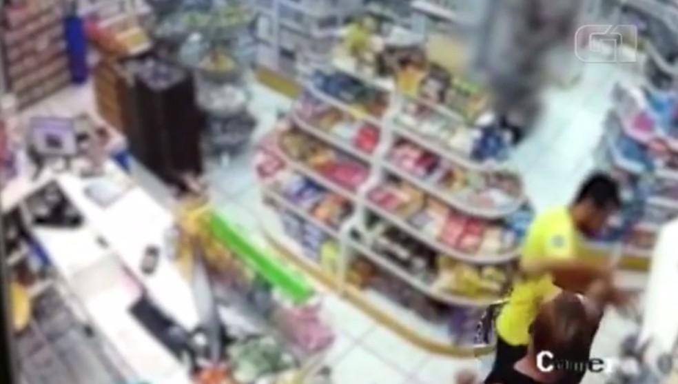 Um outro homem, funcionário da farmácia, tenta terminar com as agressões e é empurrado pelo policial — Foto: Reprodução