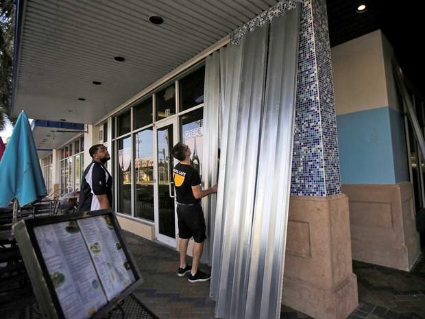 Funcionários protegem portas e janelas de um restaurante na praia de Deerfield, perto de Coral Springs, por causa da aproximação do furacão Matthew à Flórida (Foto: Henry Romero / Reuters)