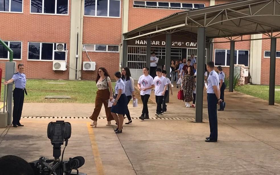 Sorrindo, grupo deixa a quarentena na Base Aérea; eles irão para nove estados — Foto: Vitor Santana/G1