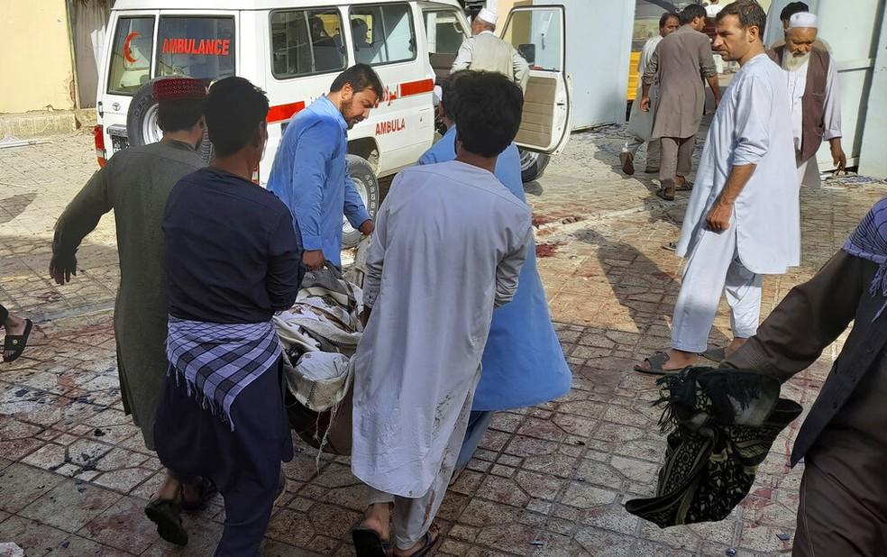 Vítima de explosão em mesquita xiita no Afeganistão é levada a ambulância, em 8 de outubro de 2021 — Foto: Abdullah Sahil/AP