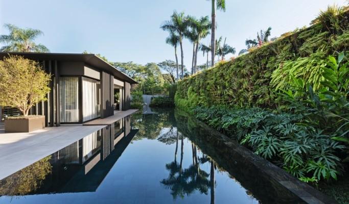 Casa contemporânea ganha jardim tropical e piscina com efeito de espelho