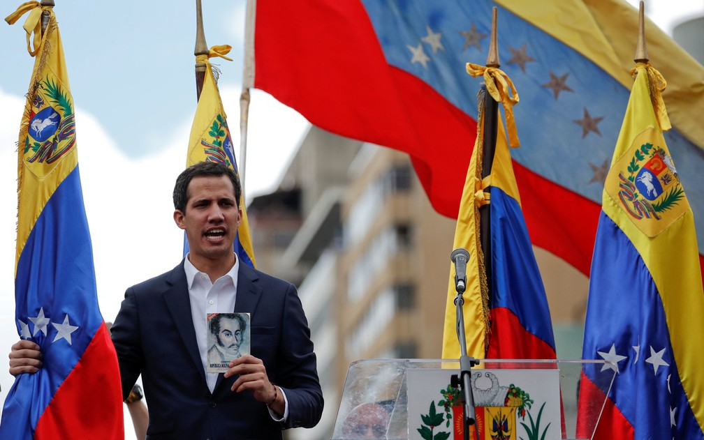 Juan Guaidó exibe cópia da Constituição e segura bandeira da Venezuela durante manifestação em Caracas na qual se declarou presidente interino do país, na quarta-feira (23) — Foto: Reuters/Carlos Garcia Rawlins