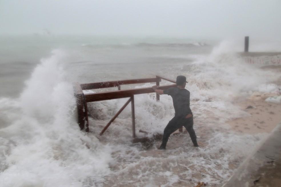 Homem tenta impedir que água leve mesa de restaurante antes da chegada de do furacão em Punta Cana, na República Dominicana  (Foto: Ricardo Rojas/ Reuters)