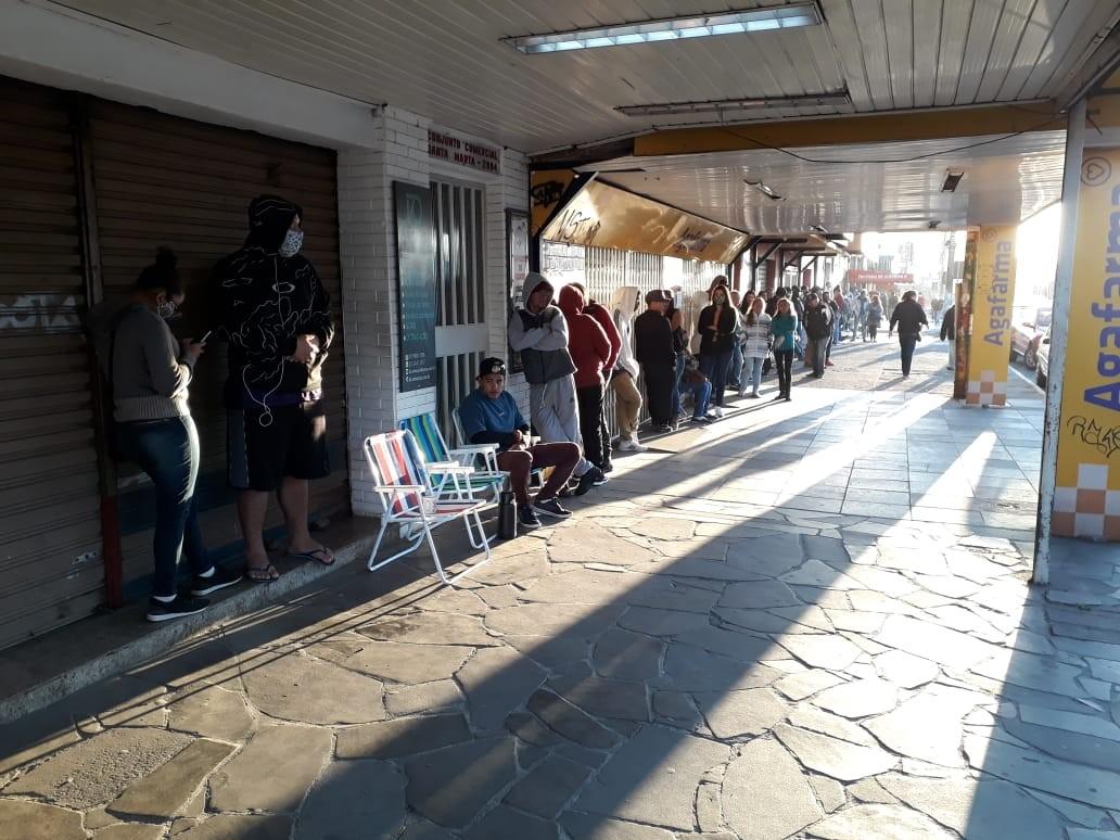 Pessoas dormem em fila da Caixa para tentarem sacar auxílio emergencial no RS