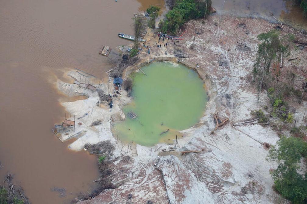 Cratera causada pelo garimpo em uma terra indígena em Roraima, na Amazônia, em maio de 2020. Foto mostra atividade sendo feita nas margens dos rios amazonenses. — Foto: Greenpeace