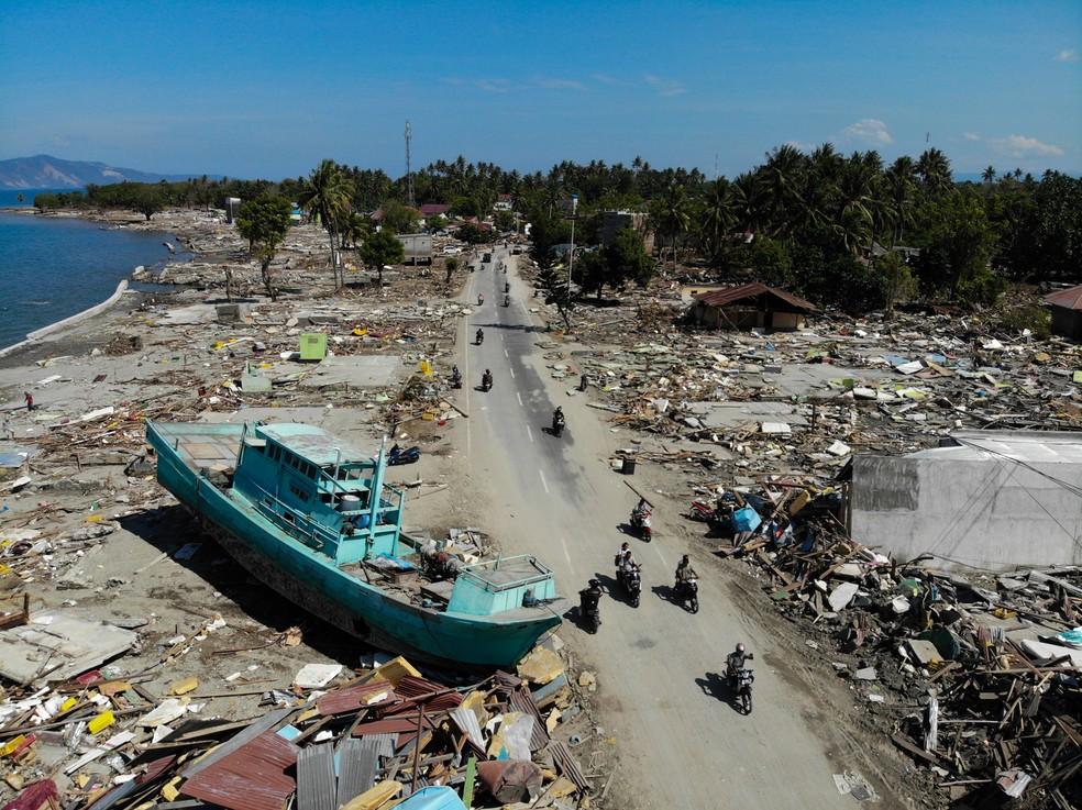 Motoqueiros passam ao lado de um barco em meio a entulhos e construções destruídas em Palu, na Indonésia, após área ser atingida por um terremoto e um tsunami — Foto: Jewel Samad/AFP