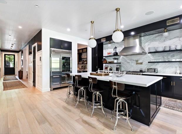 Moderna e polida, a cozinha conta com uma parede de mármore e está ligada ao jardim (Foto: Variety/ Reprodução)