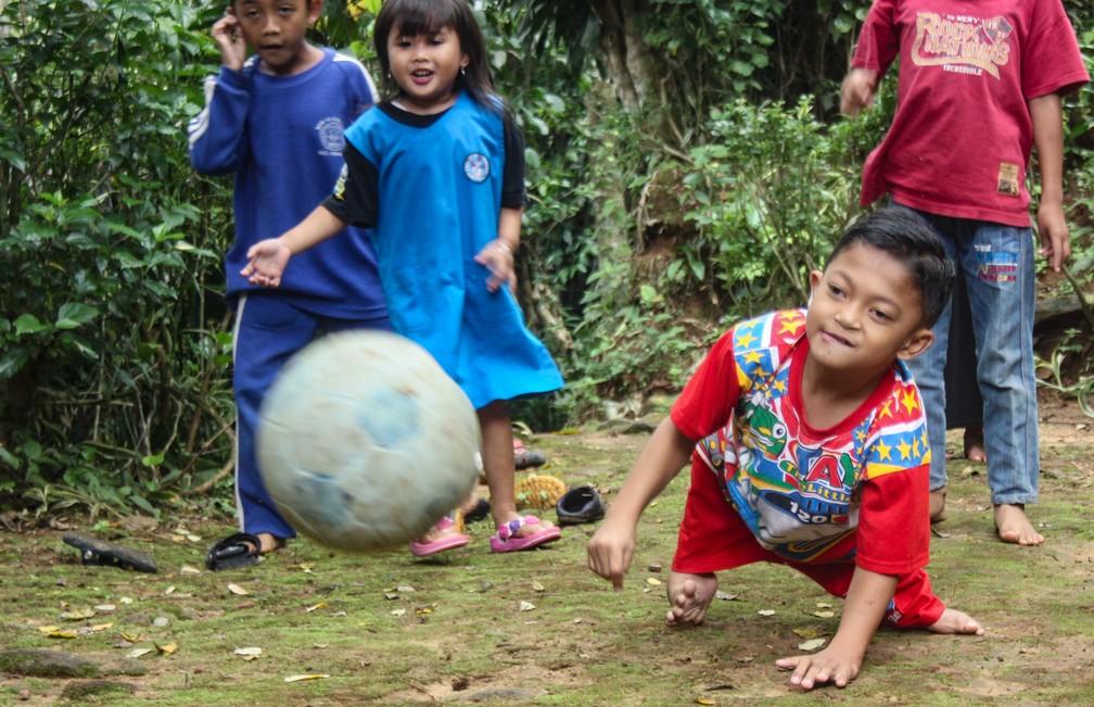 Menino indonésio com deficiência brinca com outras crianças no caminho para a escola — Foto: CANTIGIE NUR FERDINAND / AFP