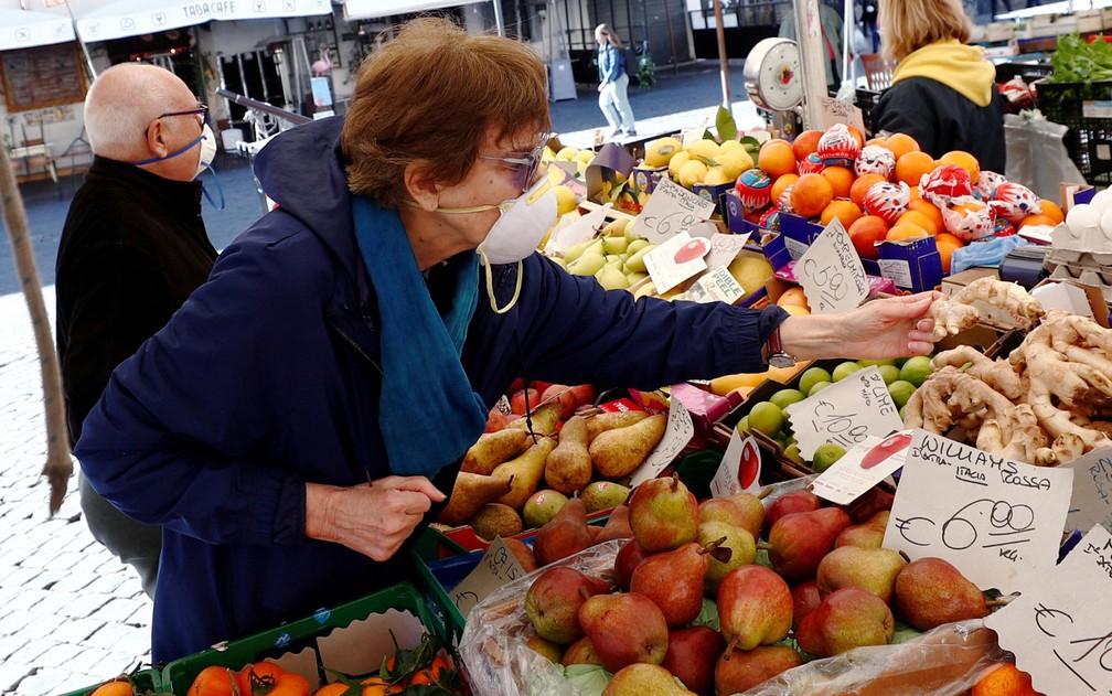 Com máscaras, clientes compram frutas no mercado Campo de' Fiori, em Roma, na Itália, na quarta-feira (11) — Foto: Reuters/Guglielmo Mangiapane
