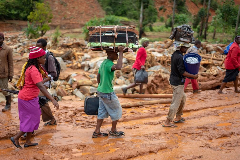 Sobreviventes deixam Ngangu levando seus pertences em malas após a passagem do ciclone Idai em Chimanimani, no Zimbábue — Foto: Zinyange Auntony/AFP