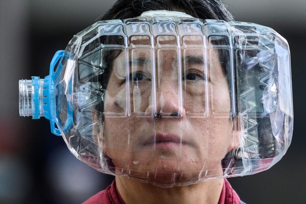 Mulher usa uma garrafa de água plástica com um recorte para cobrir o rosto em uma tentativa de se proteger da contaminação por coronavírus, em Hong Kong, em 31 de janeiro — Foto: Anthony Wallace/AFP/Arquivo