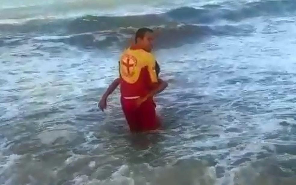 Bombeiro Carlos César resgata o jovem José Ernesto, de 18 anos, atacado por  tubarão no Grande Recife no sábado (3) (Foto: Reprodução/WhatsApp)