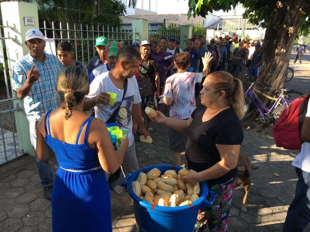 Venezuelanos recebem pão e copo de suco servido por missionárias católicas no Centro de Boa Vista — Foto: Emily Costa/G1 RR