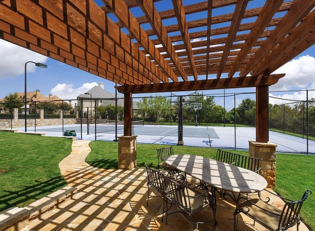 No jardim, um pergolado se estende próximo a quadra de tênis (Foto: Christie's International Real Estate/ Reprodução)