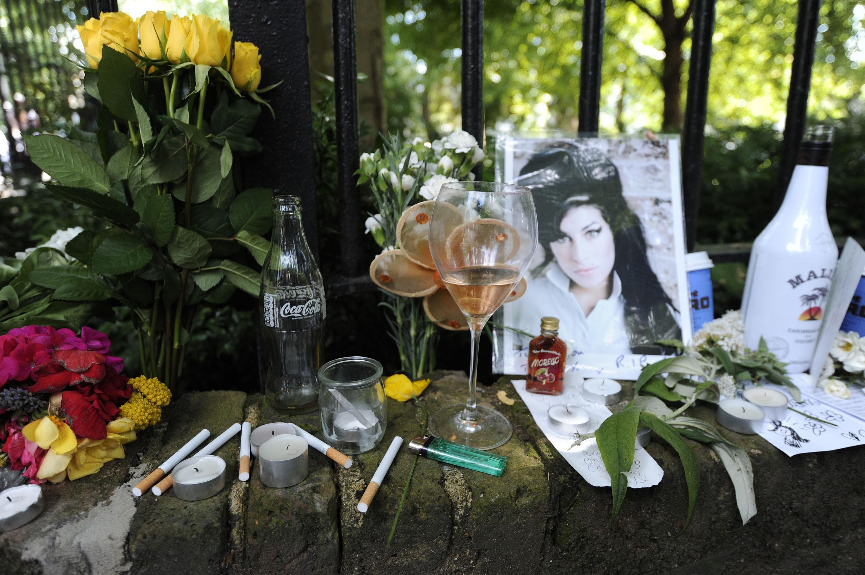 Cigarros, álcool e fotos são deixados com flores e mensagens perto da casa, onde o corpo da estrela pop Amy Winehouse foi encontrado