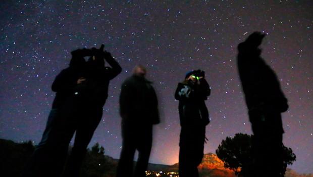 Pessoas usam binóculos de visão noturna para olhar o céu em busca de objetos voadores não identificados (OVNIs) no deserto em Sedona, no Arizona (Foto: Mike Blake/Reuters)