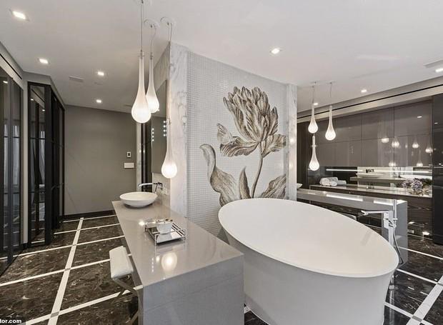Dividido em duas partes, o banheiro do quarto principal possui uma banheira e uma parede revestida por mosaico no centro (Foto: Realtor/ Reprodução)