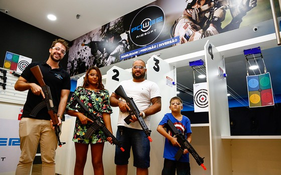 Praticantes de airsoft no Rio. A arma parece pesada para Enzo (Foto: UANDERSON FERNANDES/AGÊNCIA O GLOBO)