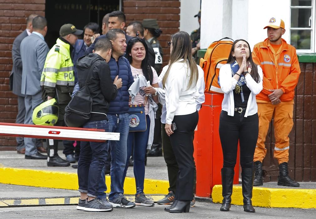 Familiares de vítimas se reúnem na entrada da Academia General Santander, em Bogotá, onde um carro-bomba explodiu — Foto: AP Photo/John Wilson Vizcaino