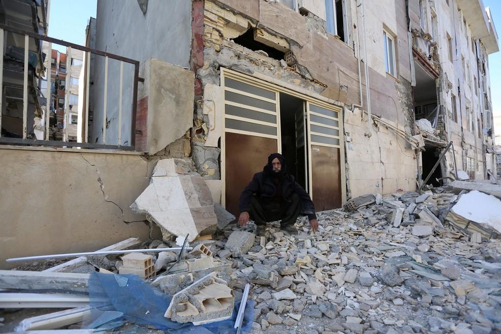 Homem é fotografado sentado sobre destroços, nesta segunda-feira (13), após tremor que atingiu a província iraniana de Kermanshah  (Foto: Tasnim News Agency/ Reuters)
