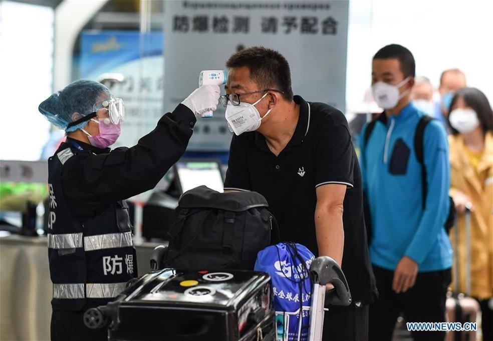 Em aeroporto na China, pessoas usam máscaras e passam por verificação de temperatura como forma de prevenção ao coronavírus — Foto: Divulgação/Xinhua/Pu Xiaoxu