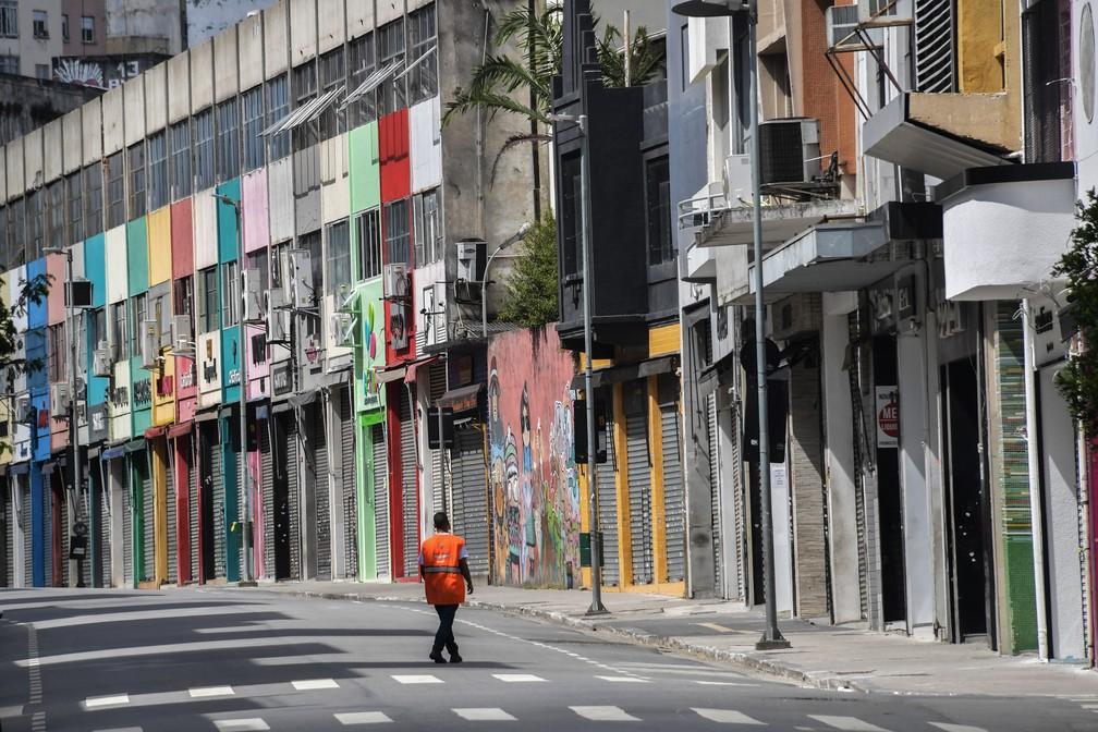 SÃO PAULO - Um homem caminha por uma rua comercial vazia no centro de São Paulo nesta terça-feira (24) depois que o governo da cidade decretou o fechamento de lojas como medida de precaução contra a disseminação do novo coronavírus  — Foto: Nelson Almeida/AFP