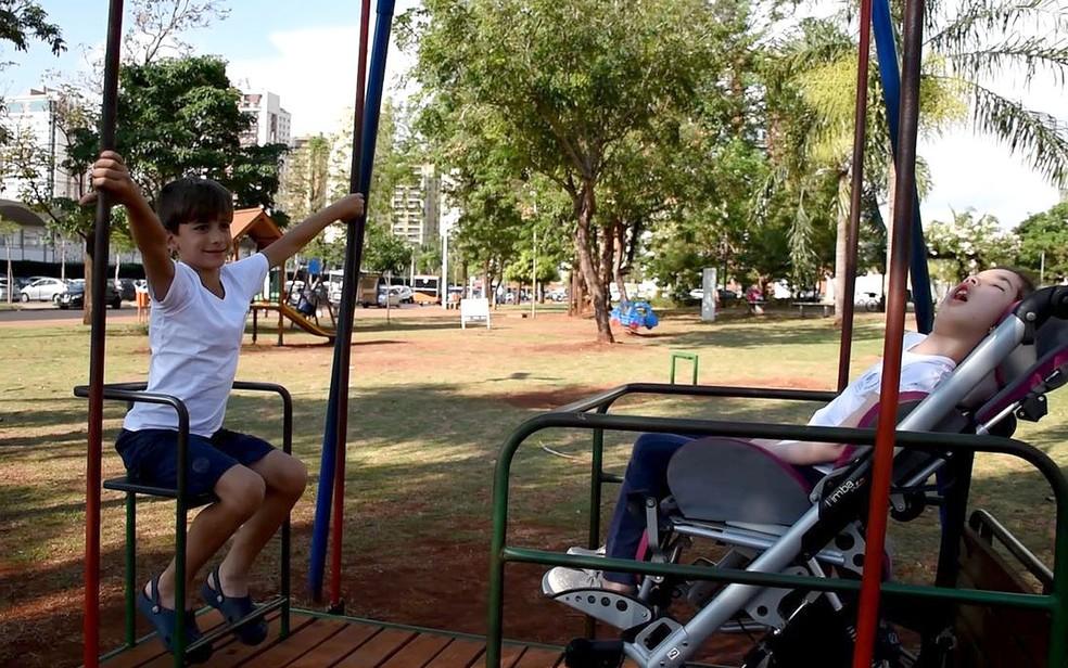 Com um balanço adaptado, as limitações de Duda não a impedem de brincar com o irmão, em Ribeirão Preto, SP — Foto: Pedro Martins/G1