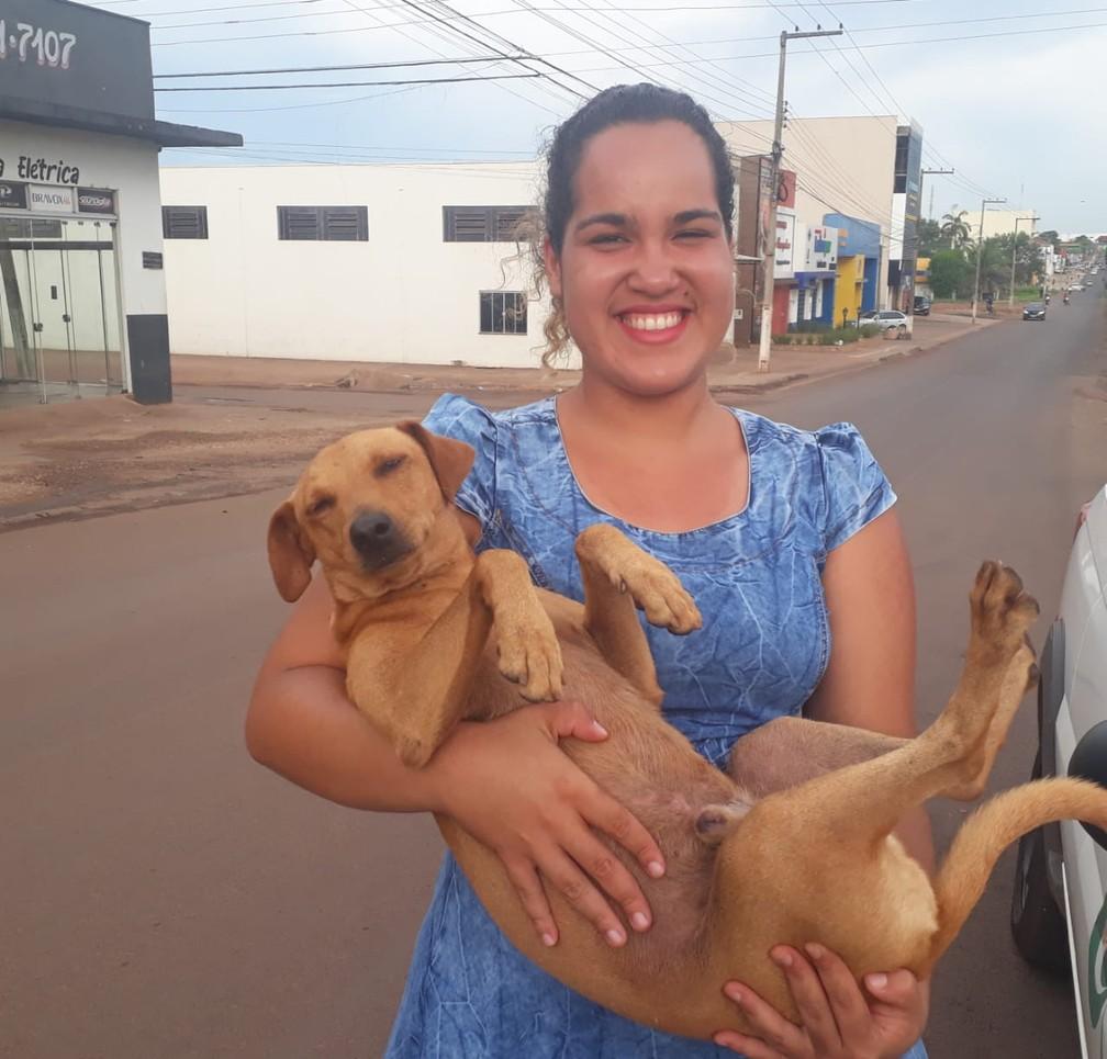 Mariana Barros de Assis, 22 anos, segura seu cachorro, que a esperou por quase 7 horas.  — Foto: Magda Oliveira/G1