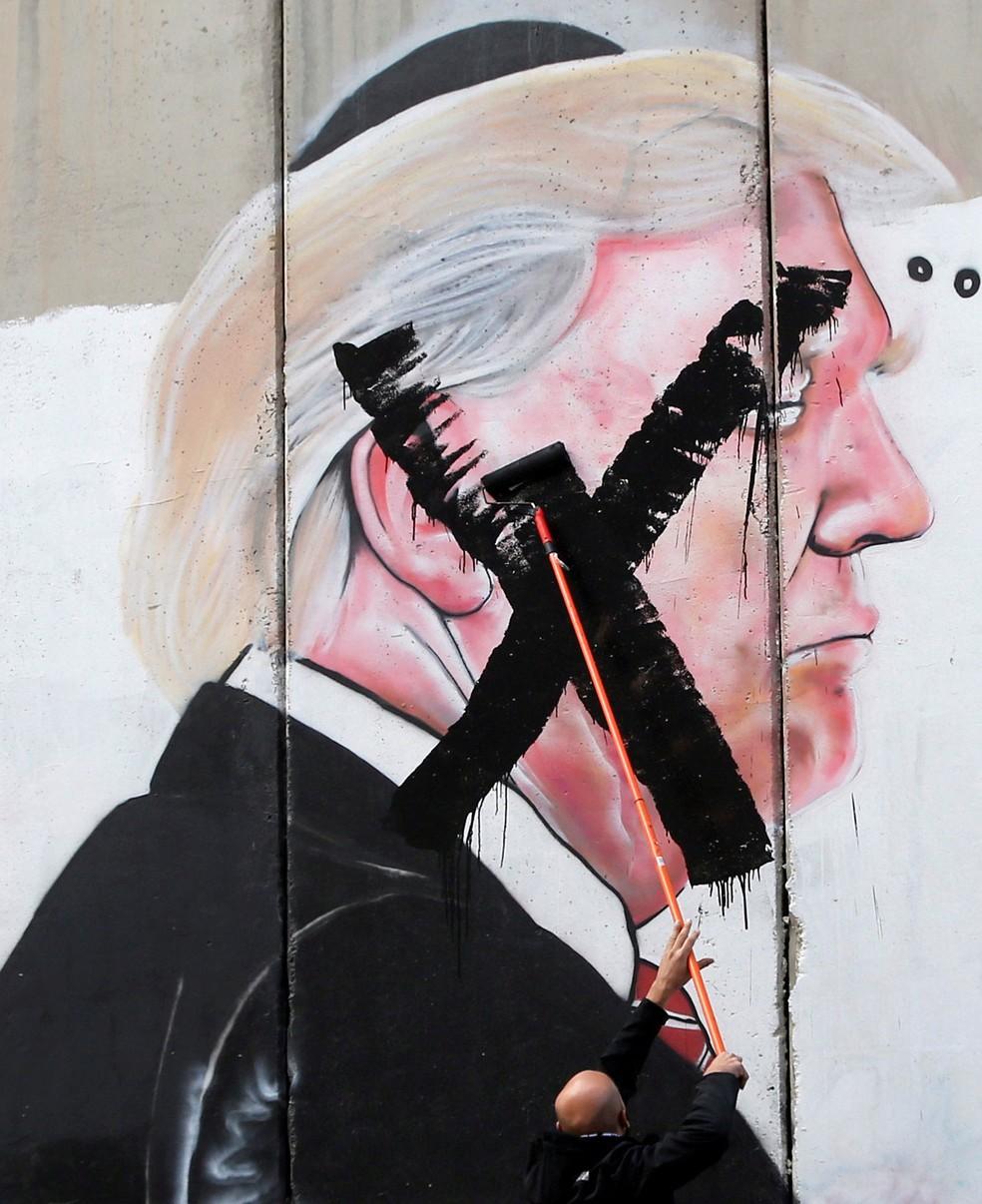 Palestino picha imagem do presidente americano, Donald Trump, pintada no muro que cerca a cidade de Belém, na Cisjordânia (Foto: Mussa Qawasma/ Reuters)
