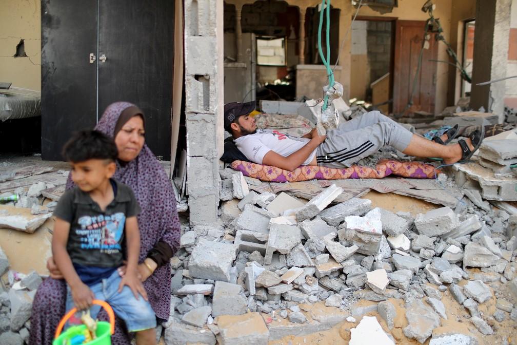 Palestino descansa entre os escombros após retornar para sua casa em Beit Hanoun, no norte da Faixa de Gaza — Foto: Mohammed Salem/Reuters