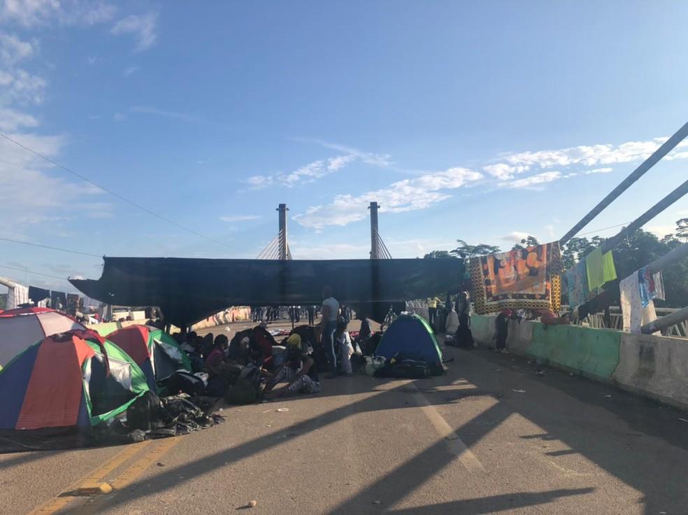 Parte dos imigrantes decidiram permanecer na Ponte de Integração para evitar a passagem de caminhões e mercadorias do Peru  — Foto: Arquivo/Assistência Social de Assis Brasil