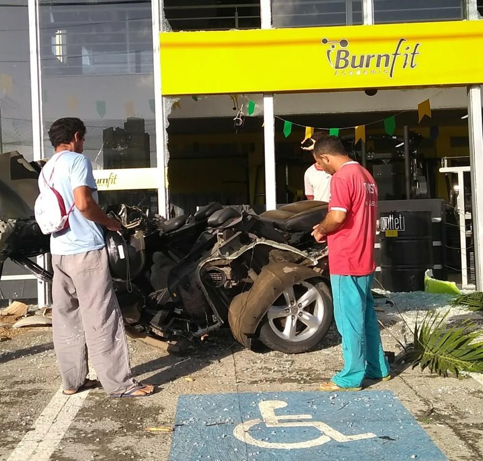 Parte do carro atingiu a fachada da academia, que teve as vidraças estilhaçadas (Foto: Luciana Cavalcante )