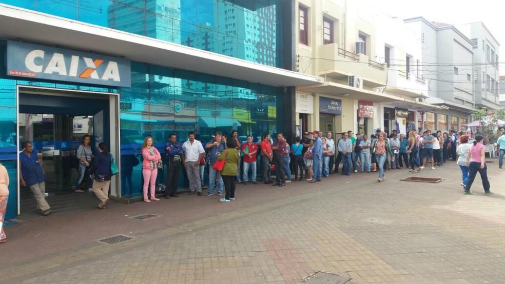 Uma grande fila de pessoas para sacar o FGTS das contas inativas já se formava diante da agência da Caixa na rua Barão do Rio Branco, em Campo Grande, uma hora antes da abertura do banco (Foto: Anderson Viegas/G1 MS)