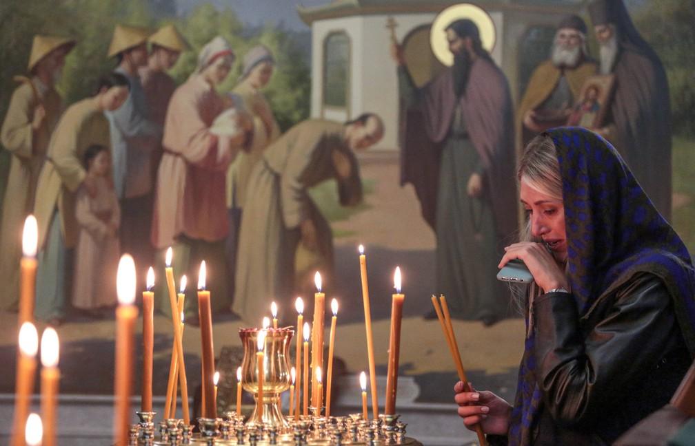 Mulher chora ao acender vela em igreja de Kerch durante cerimônia em memória das vítimas de ataque a escola da cidade — Foto: STR / AFP