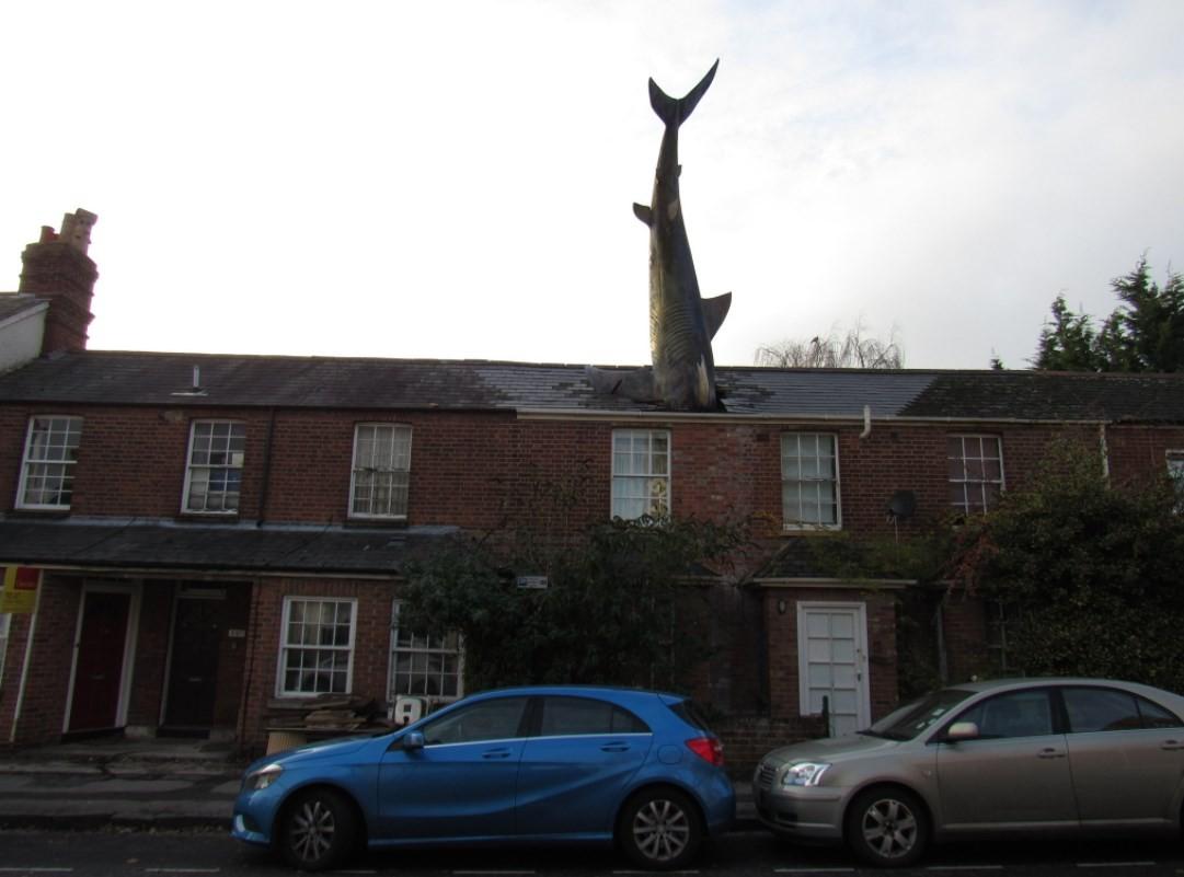 Escultura de tubarão no telhado de residência em Oxford