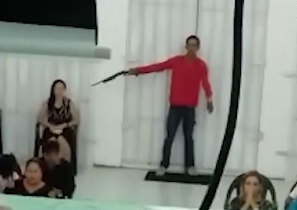 Homem aponta arma para cabeça de mulher durante culto em Manaus — Foto: Reprodução